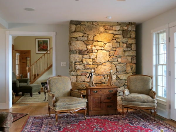 stone wall living room chair accent wall colored carpet