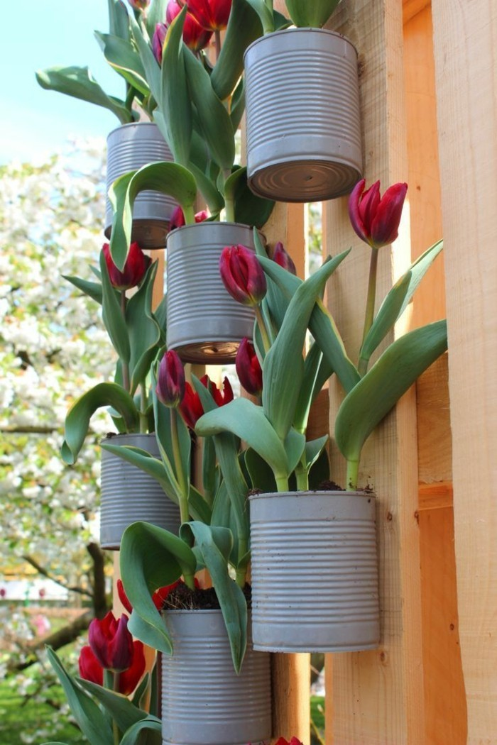 Garden decor itself make flower pots from old cans hanging on the garden fence