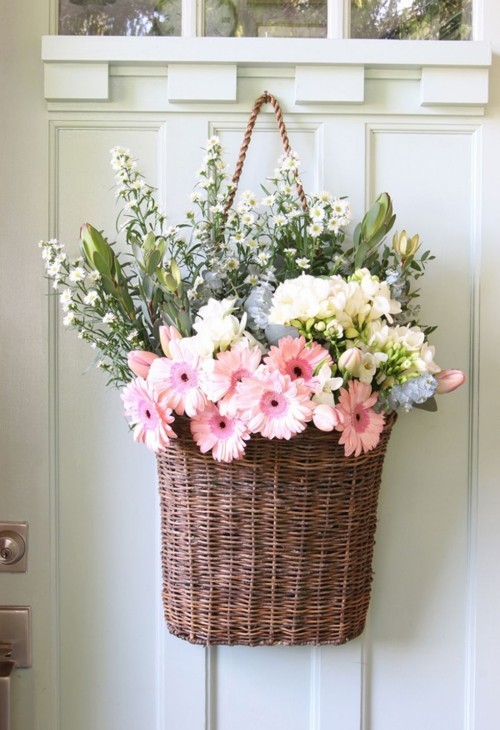 Wicker basket full of beautiful flowers at the door