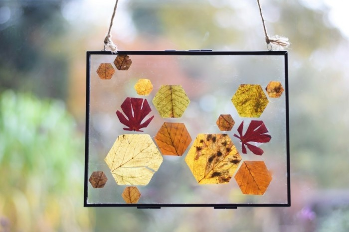 Making window pictures with children's geometry autumn leaves