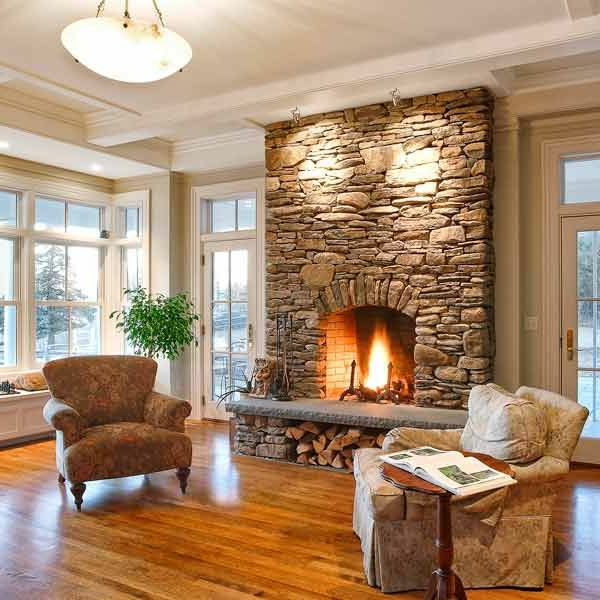 living room fireplace stone wall armchair plant