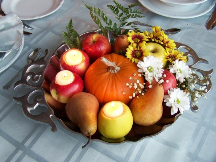table decoration for autumn with pumpkin apples and candles